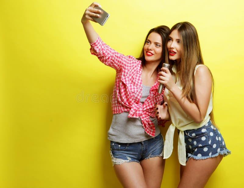 Duas meninas do moderno da beleza com um microfone tomam o selfi fotos de stock royalty free