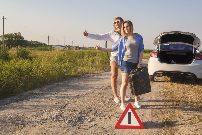 Duas meninas do motorista votam em uma estrada rural em antecipação à ajuda com um depósito de gasolina vazio e uma mangueira per foto de stock royalty free