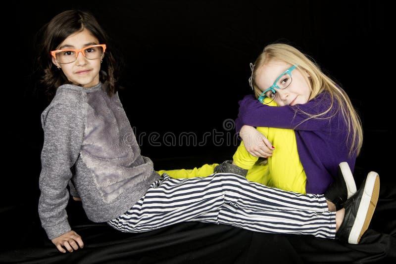 Duas meninas do preteen que sentam-se no divertimento vestindo da terra eye vidros fotografia de stock