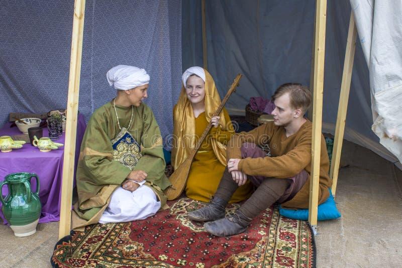 duas meninas e um indivíduo em vestidos históricos antigos brilhantes sentam-se em um tapete turco vermelho em um famoso fotografia de stock royalty free