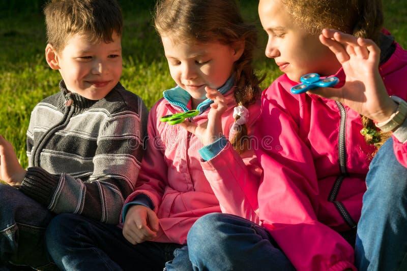 Duas meninas e um menino encontram-se na grama e no girador do jogo fotografia de stock