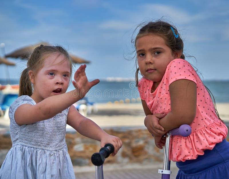 Duas meninas em 'trotinette's pela praia fotos de stock