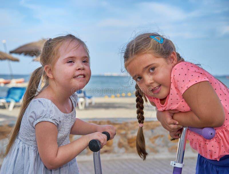 Duas meninas em 'trotinette's pela praia, ambos que sorriem imagem de stock royalty free