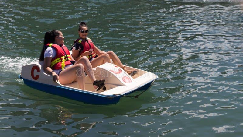 Duas meninas em um barco do pedal fotografia de stock