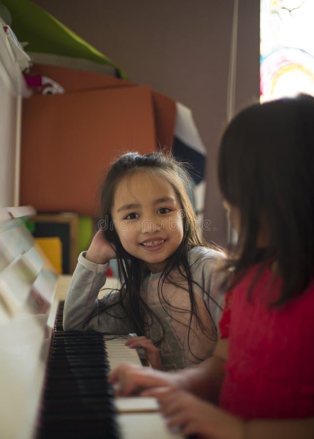 Duas meninas em uma lição de piano fotografia de stock royalty free
