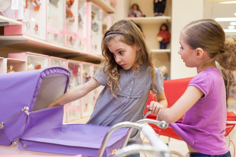 Duas meninas em uma loja de brinquedos com bonecas olham no carrinho foto de stock royalty free