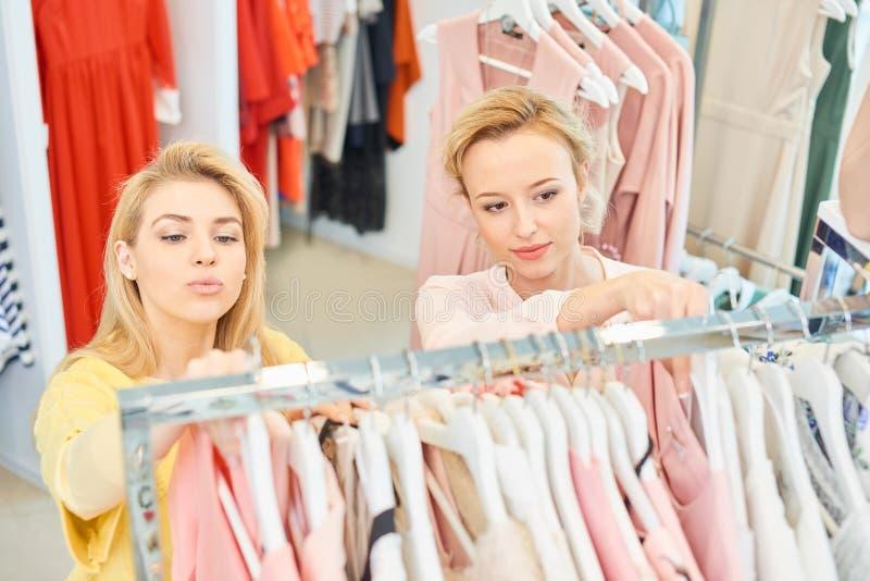 Duas meninas em uma loja de roupa imagens de stock