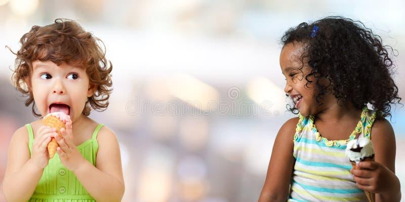 Duas meninas engraçadas da criança que comem o gelado fotografia de stock
