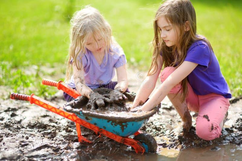Duas meninas engraçadas que jogam em uma grande poça de lama molhada no dia de verão ensolarado Crianças que obtêm sujas ao escav imagem de stock royalty free