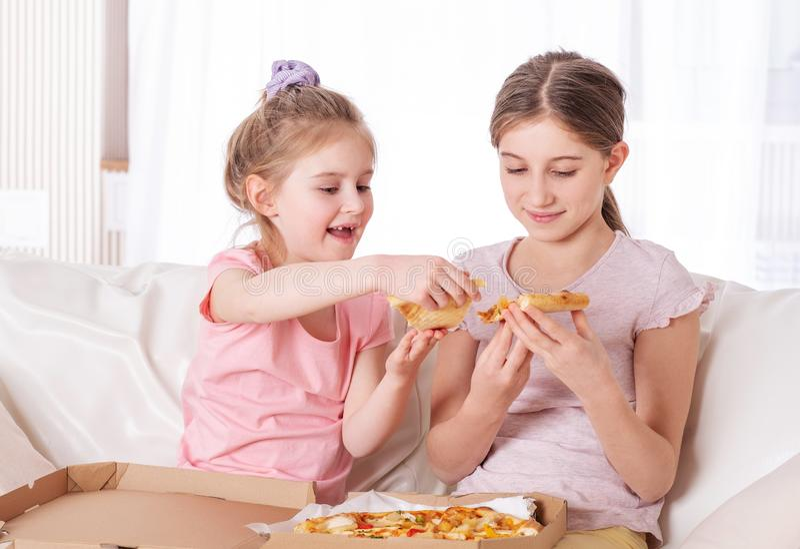 Duas meninas enjoting a pizza imagem de stock royalty free
