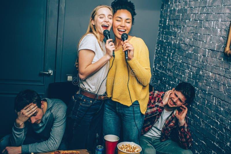 Duas meninas estão cantando uma música muito ruidosamente Seu noivo don o ` t como porque as jovens mulheres don o ` t canta muit imagens de stock