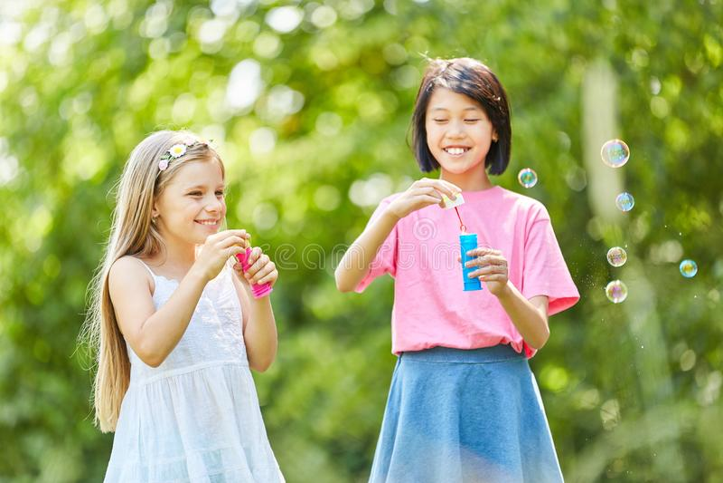Duas meninas estão fazendo bolhas de sabão imagens de stock royalty free
