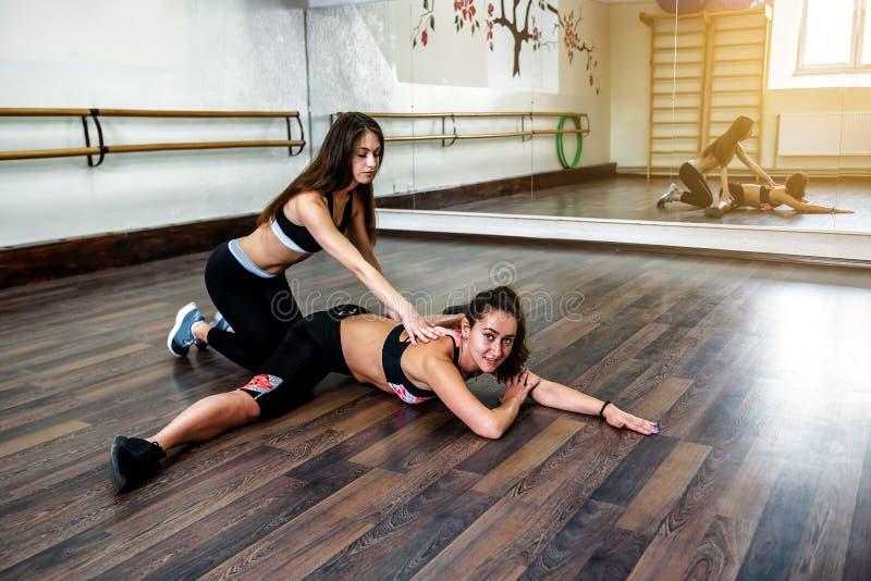 Duas meninas estão fazendo a ioga, ginástica aeróbica, exercícios dos pilates foto de stock royalty free