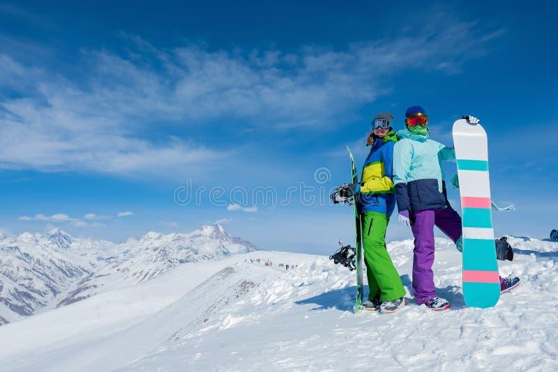 Duas meninas estão guardando placas do snowboard Inverno As montanhas fotografia de stock royalty free