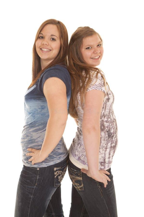 Duas meninas estão para trás para suportar imagens de stock