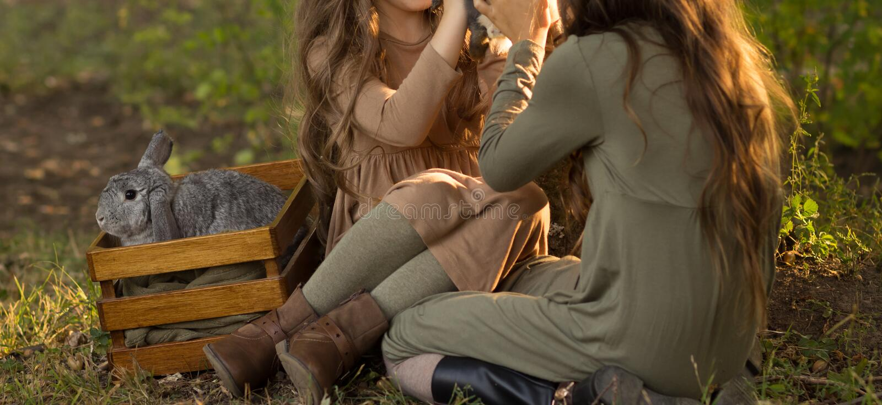 Duas meninas estão sentando-se sob uma árvore nos coelhos pequenos da grama e das trocas de carícias, guardando um grande coelho  fotos de stock royalty free