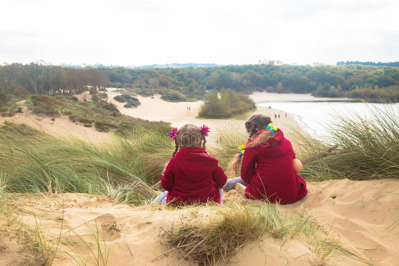 Duas meninas estão sentando-se sobre uma duna de areia fotografia de stock