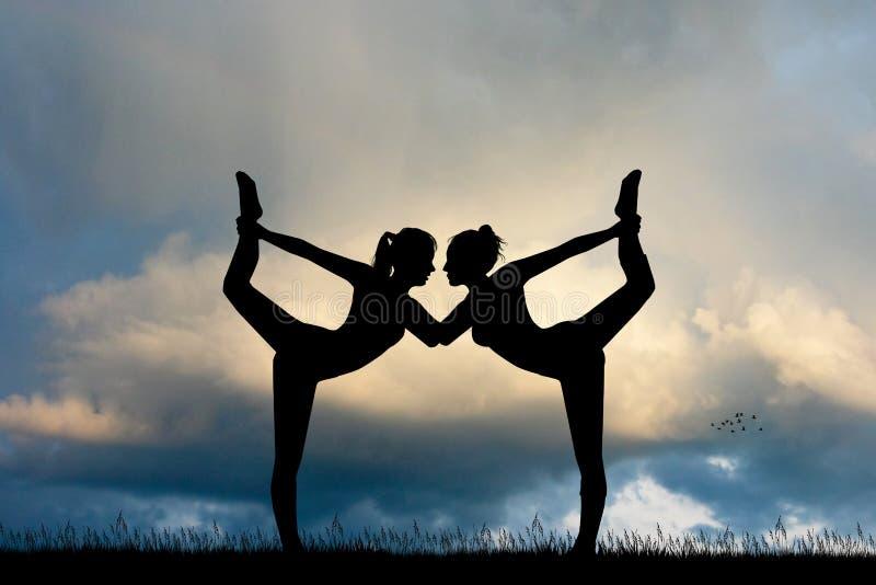 Duas meninas fazem a ioga no por do sol ilustração stock