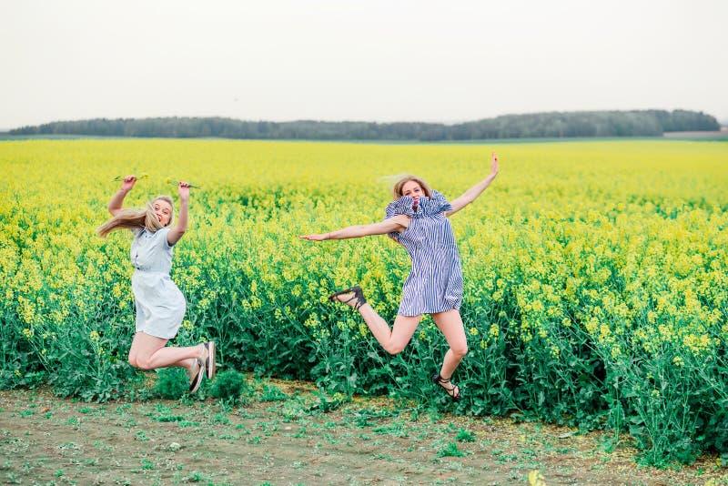 Duas meninas fazem um salto no campo da colza imagem de stock royalty free
