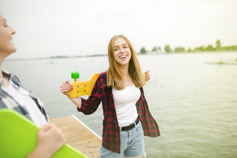 Duas meninas felizes alegres do skater no equipamento do moderno que tem o divertimento em um cais de madeira durante férias de v imagem de stock
