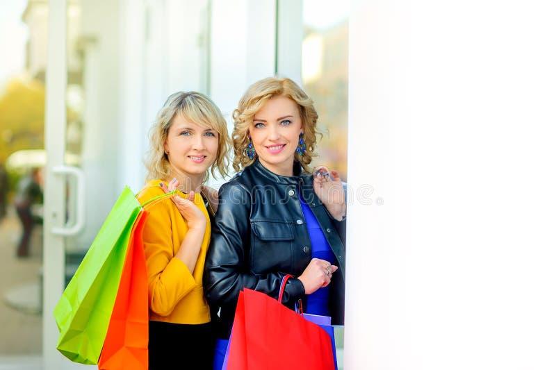 Duas meninas felizes com posição de sorriso dos sacos de compras perto da janela fotografia de stock