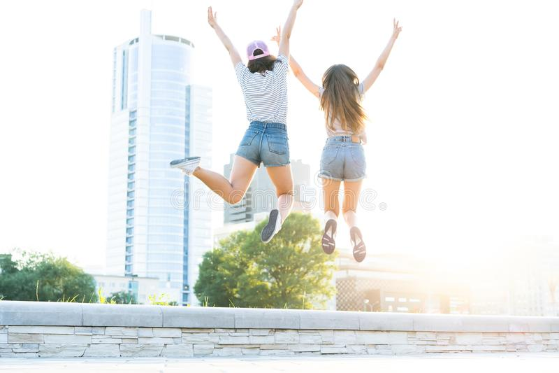 Duas meninas felizes novas do moderno que têm o divertimento, sorrindo, rindo, saltando, andar exterior na rua, verão relaxam fotografia de stock royalty free