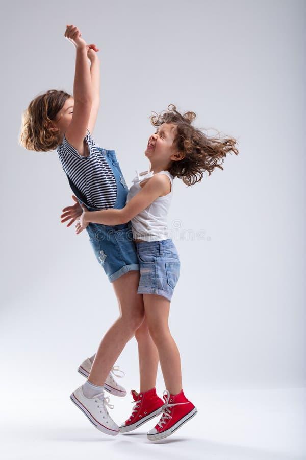 Duas meninas felizes que abraçam e que saltam fotografia de stock