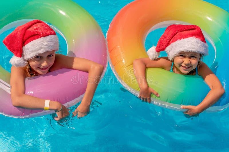 Duas meninas felizes que flutuam em uma associação azul em chapéus de Santa em um fundo azul, no olhar na câmera e no sorriso Con fotografia de stock