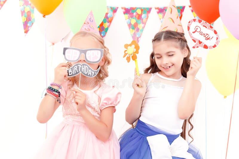 Duas meninas felizes que jogam com etiquetas do aniversário fotos de stock