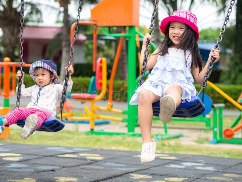 Duas meninas felizes que jogam o balanço no campo de jogos Feliz, F imagem de stock royalty free