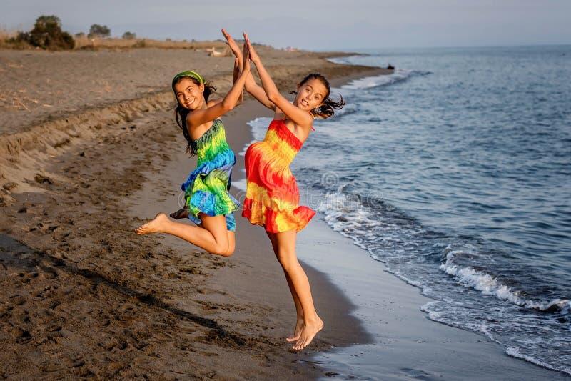 Duas meninas felizes que saltam no ar na praia fotografia de stock