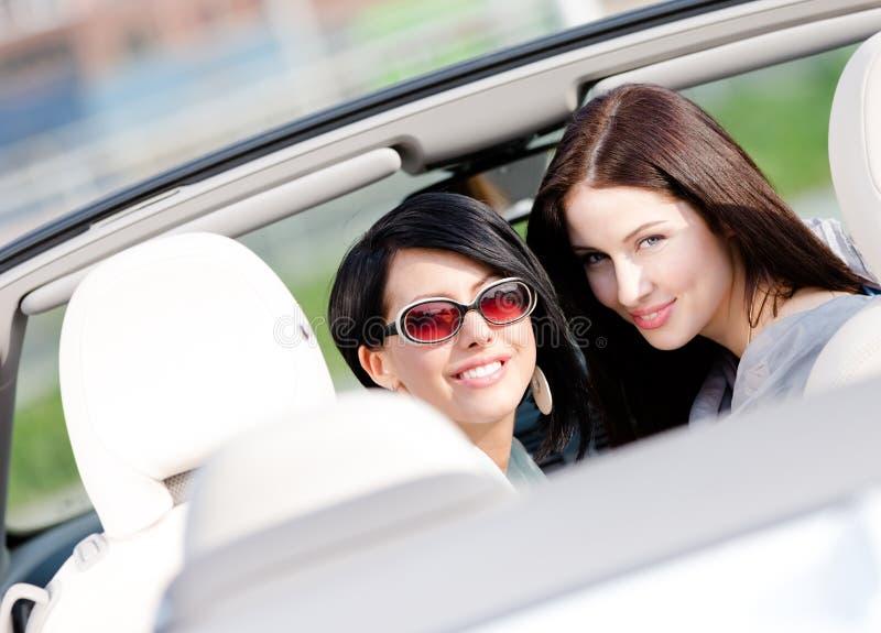 Duas meninas felizes que sentam-se no cabriolet gerenciem para trás fotografia de stock