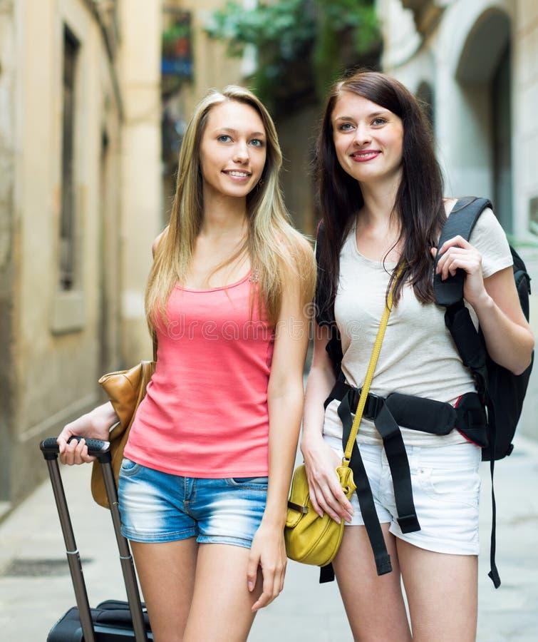 Duas meninas felizes que sorriem na estrada ao hotel a pé imagem de stock