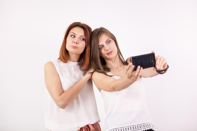 Duas meninas felizes que tomam um selfie fotografia de stock