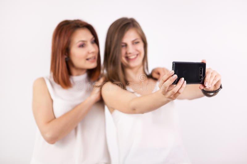 Duas meninas felizes que tomam um selfie imagem de stock