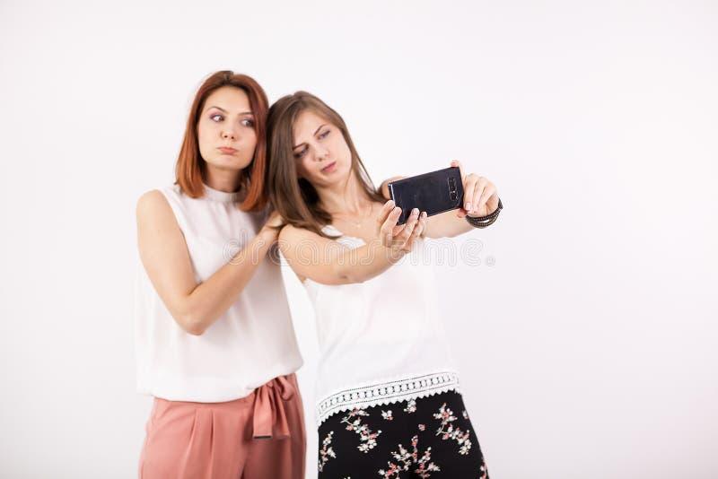 Duas meninas felizes que tomam um selfie imagens de stock royalty free