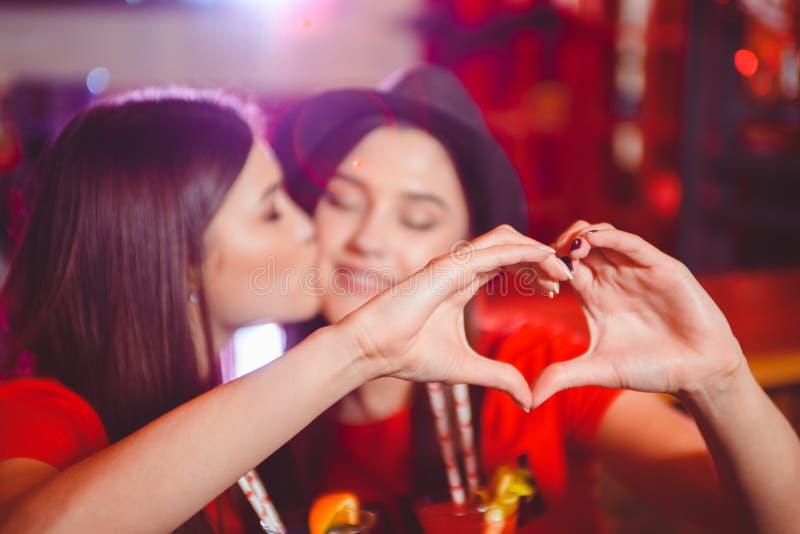 Duas meninas lésbicas novas beijo e para fazer um coração com suas mãos em um partido do clube foto de stock royalty free