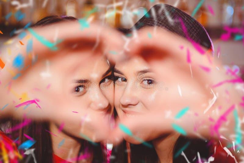 Duas meninas lésbicas novas fazem um coração com suas mãos em um partido do clube fotos de stock royalty free