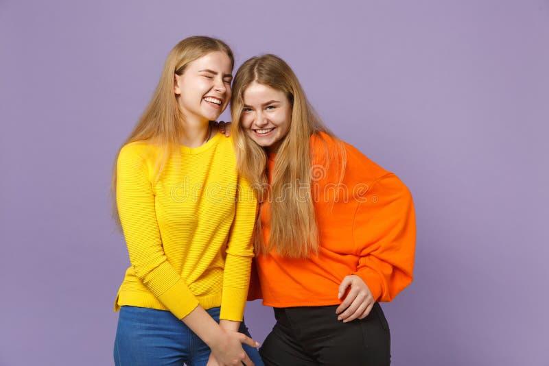Duas meninas louras novas consideravelmente felizes das irmãs dos gêmeos na posição colorida vívida da roupa que olha a câmera na fotografia de stock