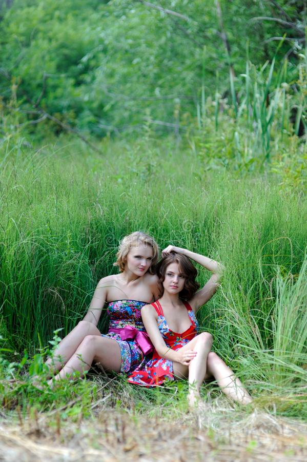 Duas meninas louras novas e a mulher moreno nos vestidos brilhantes que levantam no verão estacionam na grama alta imagens de stock