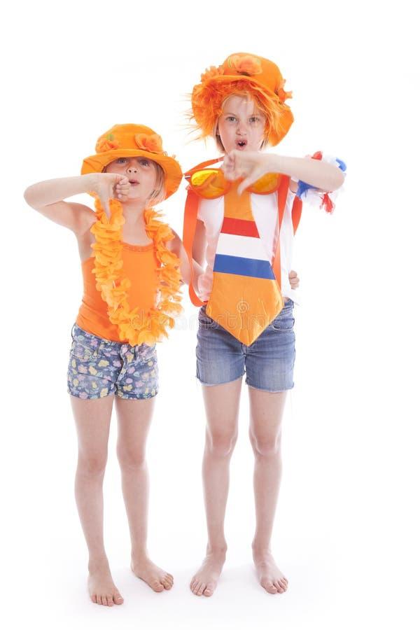 Duas meninas na laranja com polegares para baixo fotografia de stock