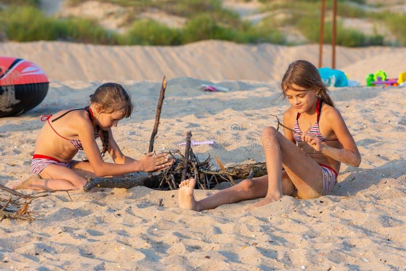 Duas meninas na noite na praia preparam um lugar para um fogo fotografia de stock
