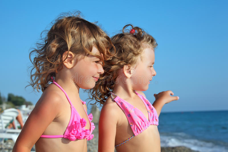 Duas meninas na praia, olhando longe imagens de stock