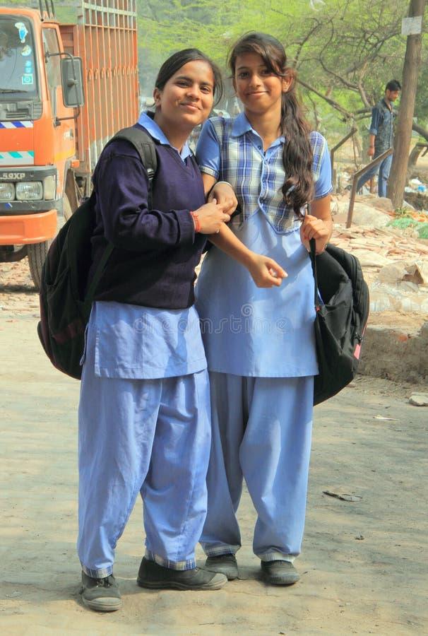 Duas meninas na roupa da escola estão sorrindo a alguém fotografia de stock royalty free