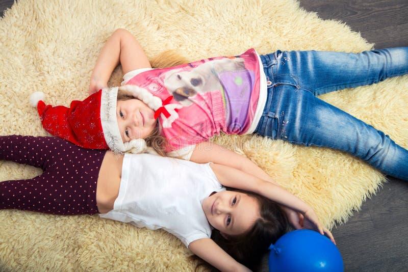 Duas meninas no assoalho, jogando em casa, vista superior imagens de stock