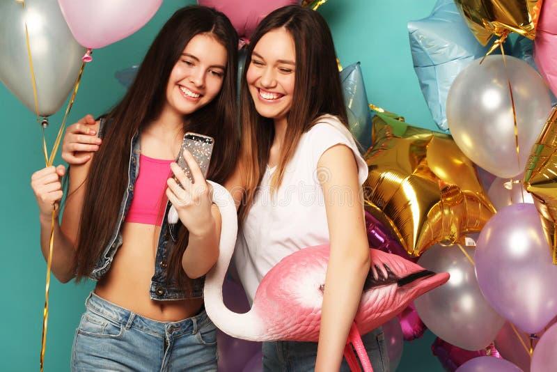 Duas meninas no equipamento à moda do verão, nos vidros de papel e no bal do ar imagem de stock royalty free