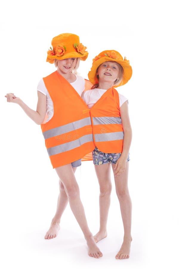 Duas meninas no equipamento alaranjado imagem de stock
