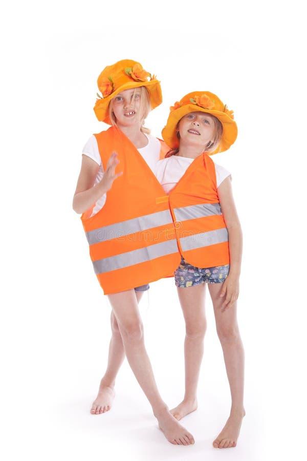 Duas meninas no equipamento alaranjado foto de stock