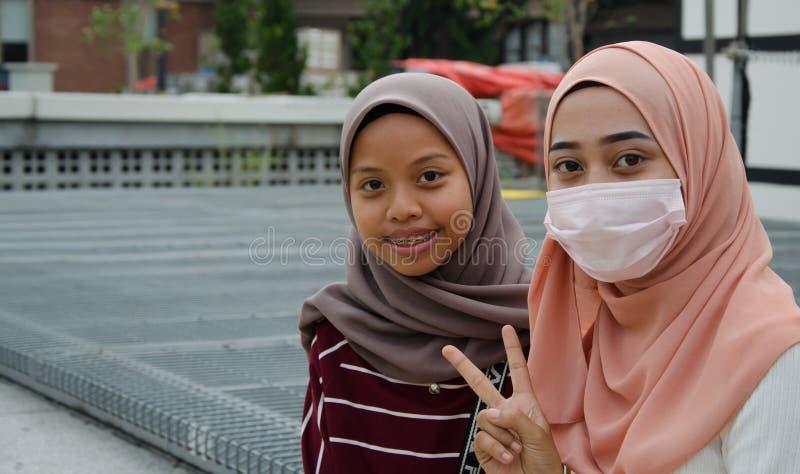 Duas meninas no hijab, um deles que vestem uma máscara imagens de stock royalty free