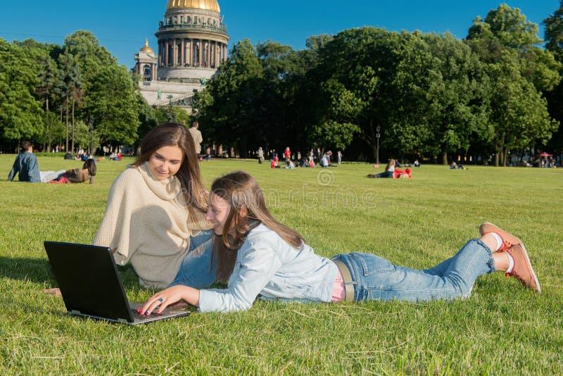 Duas meninas no parque com um portátil fotografia de stock royalty free